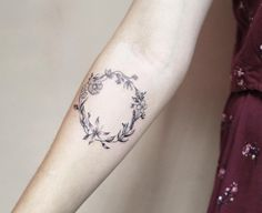 Elegant floral crown tattoo by Luiza Oliveira