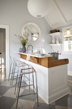 Stylish and inviting, this intimate home bar makes entertaining classy and fun. Love the Lucite and chrome bar stools.
