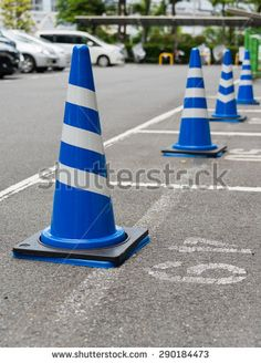 Traffic cones painted in blue and white standing in a row at a parking lot - stock photo
