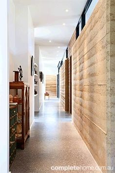 Rammed earth internal wall - hallway. Looks good with concrete flour , white, and lots of light.