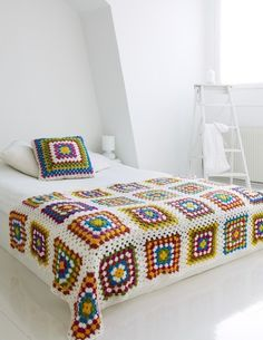 granny square bedspread looks stunning in an all white room, though I'd go with a slightly different color combo for something even more beautiful......
