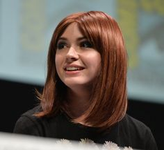 Karen Gillan whips off her wig during a press conference to reveal her bald head