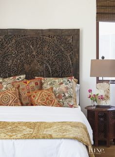 A carved teak headboard and decorative sea life-themed pillows create a island getaway ambience in this Balinese-esque guest bedroom. A weathered coral stone lamp lends an organic touch. Bed Headboard Design, Wood Headboard, Headboards For Beds, Headboard Ideas, Panel Headboard, Panel Bed, Home Bedroom, Bedroom Decor, Master Bedroom