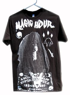 The magic hour is upon when the veil is thin revealing all kinds of ethereal horror and mysterious weirdness: a black cat, a dagger, an eye - even the grim reaper appears to connect to the living through the ouija board.  Printed on a soft black cotton tee.  Our unisex tees are 4.2 oz., preshrunk 100% combed ring-spun cotton. Available Sizes: S, M, L, XL, 2XL, 3XL