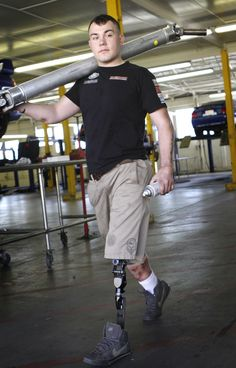 """Marine Cpl. Tim Read """"humps"""" a driveshaft across the floor of the Marine Corps Recruit Depot hobby shop garage in San Diego, California on December 19, 2012. When the infantryman was humping weapons on patrol in Afghanistan he was horribly wounded by an enemy explosive device.  It took his left leg and mangled his right one. He says working on his car and teaming up with like-minded Marine gearheads gives him a renewed sense of belonging and accomplishment. (Don Bartletti/Los Angeles…"""