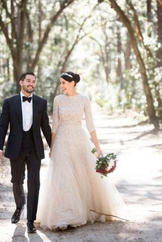 Bride in long sleeve lace wedding dress with groom in tuxedo walking through trees palmetto bluff