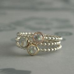 This has to be my favorite set right now! So fresh and fashionable! Wear them alone or stack them together, moondrops will be your new favorite ring!  This listing is for the entire set of 3 moondrop rings. Each one is handmade from sterling silver 1.6mm wide beaded wire. A bezel (one each in solid 14K rose, white and yellow gold) is securely soldered to each band and set with a 4mm genuine AAA grade rose cut rainbow moonstone. The entire ring is meticulously hand polished to a high shine…