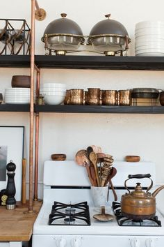 The light-filled kitchen features a bevy of warm metals, including rustic copper piping and tableware. Kristan Cunningham