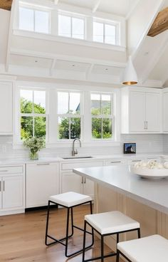 Such a stunning kitchen with transom windows + clerestory windows + large windows over the sink + black and white counter stools + wood stained island Clerestory Windows, Dormer Windows, Transom Windows, Large Windows, Kitchen Interior, Kitchen Design, Kitchen Decor, Window Over Sink, Dark Accent Walls