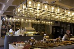 I like this set up. Simple array of oversized mason jar lighting. ( Food hall at the Barbican in London )