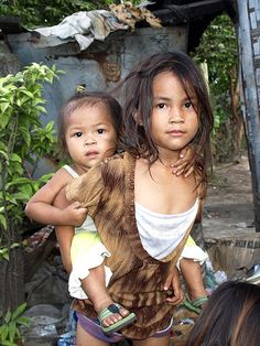 """The family is very important in the Philippines. Here the older sister ( called """"Ate"""") is taking care of the younger one ..."""