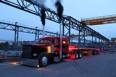 Black and red Peterbilt w/flat deck trailer