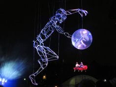 Giant Marionette - Calgary Stampede Grandstand Show. A giant marionette over 38 feet tall rises out of the stage. In one hand it carries children in the sky. In the other, it holds a moon with a maiden in it on a trapeze.