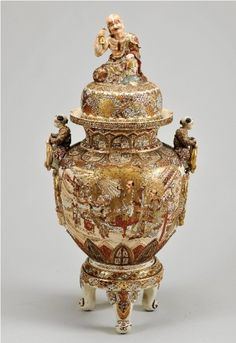 A large Meiji Period Satsuma Porcelain Vase, with gilt relief and decorated with figural scenes, the twin handles and the top of the cover applied with modelsc of Oriental figures, on atripod base. vcirca late 19th century