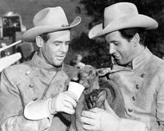 """Robert Ryan and Rock Hudson make a new acquaintance while filming """"Horizons West."""""""