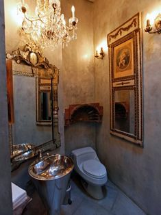 A hanging chandelier and gold framed mirror give this vintage bathroom plenty of character.