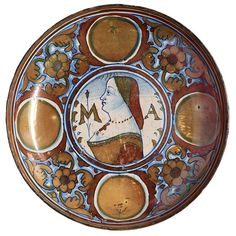 Italian Renaissance, this Majolica plate, made of clay, is decorated with gold, copper, blue and beige glazes.  Typical for this time, 1519, is the woman's profile bust.  The plates were generally created as engagement or wedding gifts.   Photo:  Piermont Public Library and Museum