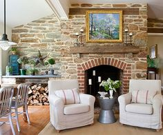 One of the most fundamental features in a rustic living room is the fireplace. Consider dressing yours in authentic native rock, which brings the rugged beauty of the outdoors inside. A brick border outlines the curve of this fireplace, giving it a graceful note. White, transitional club chairs lighten the look and provide a comfy spot to enjoy the fire.
