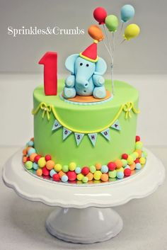A colourful circus themed first birthday cake featuring an elephant and balloons.