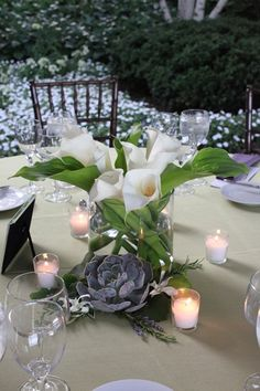 Classic,  low arrangement of traditional, beautiful white trumpet and green goddess calla lilies.  Artful silvery lavender succulentsand fragrant sprigs of lavender, rosemary, scented geranium and galax foliage surround arrangement, while classic votive candles cast a little glow.