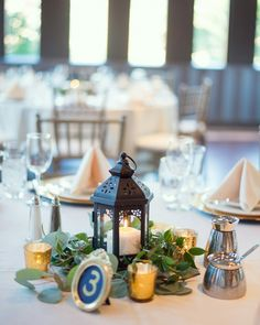 Lantern and ruscus/eucalyptus centerpiece with gold framed table number. I LOVE how they turned out!!
