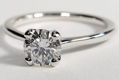 Beautiful, simple and elegant solitaire engagement ring. The thin (or as they call it, 'Petite Nouveau') band is made of gorgeous 18k white gold and will make your diamond really pop. Slightly less versatile than other solitaire rings, this one can only be set with a round, Asscher, cushion, or radiant shaped diamond.
