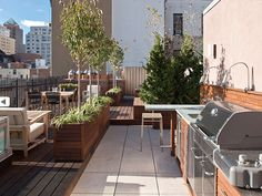An outdoor kitchen on a rooftop in New York. Notice the L-shaped layout of the counter and the bendable task lighting.