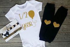 Celebrate your daughters 6 months old Birthday in style with this half year girls gold glitter bodysuit set featuring our popular balloon design on a white bodysuit! Complete with a handmade, black/gold/ & white headband set, and black leg warmers with gold heart patches.