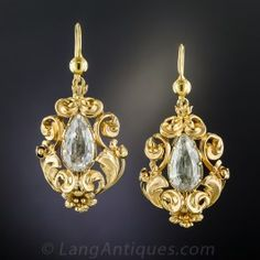 Rendered in 15ct. yellow gold in mid-19th-century Great Britain, these rare and ravishing Victorian ear drops feature a pair of bright sky blue foil-backed aquamarine pear shapes enveloped in flowing, multidimensional scroll and floral golden repoussé. 1 1/4 by 3/4 inch, not including the newly added ear wires.