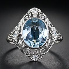 From the turn-of-the-twentieth century - the Belle Epoch - comes this superb and ravishingly beautiful original Edwardian aquamarine ring. A serene and tranquil pastel blue faceted oval aqua is bezel set atop an exquisitely fashioned platinum mounting embellished with graceful open scroll work, delicate hand-engraving and dotted with four twinkling European-cut diamonds.