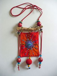 Fransien de Vries - embroidered and beaded with rings to hang from the wooden piece.