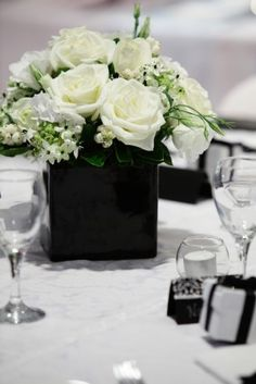 small black vase for smaller flower arrangements (one on either side of main center piece) accompanied with white candle votives
