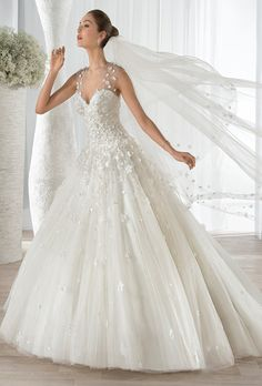 Demetrios. Dreamy sleeveless, tulle ball gown features a sweetheart neckline and unique flower embroidery throughout the bodice and skirt. Sheer illusion overlay transitions into a low, illusion back with buttons.