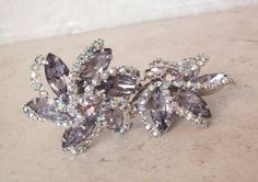 Weiss Lavender Earrings Prong Set Rhinestone AB Clip On Floral Swirl Starburst Vintage 051116BT by cutterstone on Etsy #Weissearrings #vintageearrings #purplerhinestones #floral #starburst #auroroborealis