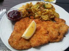 Piatto tirolese wienerschnitzel con patate e marmellata di mirtilli rossi