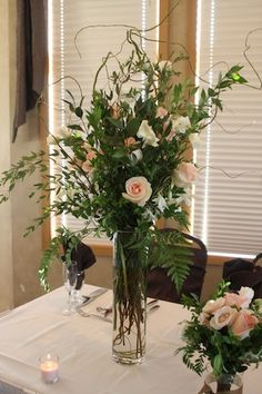 An altar arrangement using roses, calla lilies, lisianthus, dendrobium orchids and curly willow.