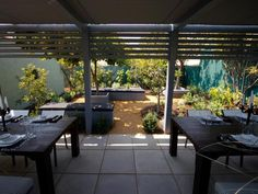 Jamie removed the unkempt lawn, replacing it with this classy covered dining area. He also created enclosures for the original fruit trees and added benches for extra seating.