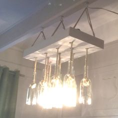 It took a while to collect the bottles, but I have finished the wine bottle chandelier #2 for the dining area! It is made of 11 bottles tied to a wooden support with rustic rope.