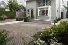 Tuinontwerp en tuinaanleg Eindhoven Helmond voortuin oprit van gebakken klinkers met border.