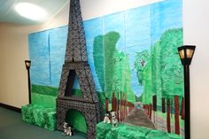 Our office decorated for Party Day theme of Paris! Mural hand painted by my colleagues. The Eiffel Tower constructed from cardboard boxes, paint and black tape. Hedges are boxes covered in painted crumpled paper. Lamp posts made from poster tubes.