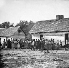 Photo of a group of 30 plantation slaves gathered around a large slave cabin located on Smith's Plantation, Beaufort, South Carolina.