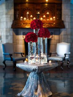 tall red rose centerpiece! Everything can be white and gold. Do tall simple clear vase with clear marbles maybe gold ribbon and do red roses? Not too much red but still incorporates it