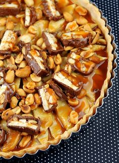 Snickers Apple Tart (Salad  )  1 premade pie crust  2 large granny smith apples, peeled and sliced  2 Snickers bars, chopped  ¼ cup unsalted, dry roasted peanuts  ¼ cup heavy whipping cream  4 TBSP brown sugar  1/3 cup caramel sauce