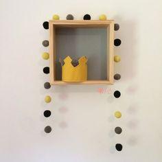 Guirlanda de Bolinhas de Feltro Combinação Amarelo, Cinza e Preto para decoração de quartos e festas infantis. Junto a ela, nosso nicho quadrado (30cm x 30cm x 10cm) feito em madeira maciça com fundo cinza.