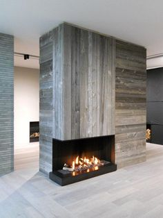 A modern fireplace with wood paneling for a mountain home. Not sure the wood should go all the way down to the fireplace