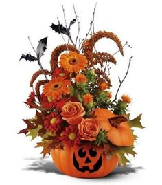 pumpkin flower arrangement with bats made from holly