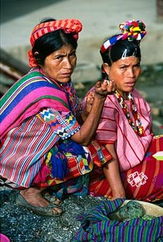 Guatemala ~ To the trained eye these two women tell a story. Both wear the skirt of San Idelfonso, however the woman on the left wears a different head-band and huipil from the neighboring community of Petzal. She may have married into a San Idelfonso family yet through her dress, she preserves aspects of her heritage.