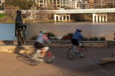 Bike riders zoom up and down the Lady Bird Lake hike and bike trail, past the…