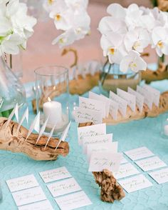 Seaside vibe of the textured aqua linens, palm fronds, and candles.