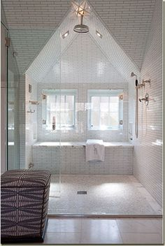 Shower and tub behind frameless glad enclosure. Notice transitions from large field tiles to small ones on the wet area (better traction). Walls and ceilings entirely in tile.